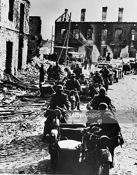 German motorcycle troops travel through a town in Poland heavily damaged by bombing 1939