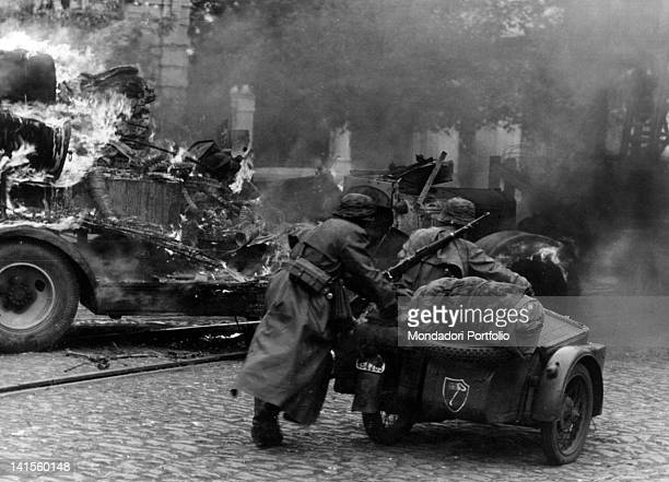 German motorcycle with sidecar advances among flaming wreckage in a street Mariupol' October 1941