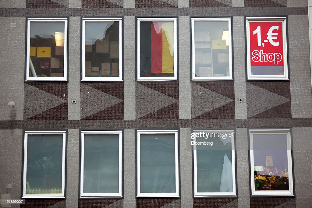 A German national flag and a one euro sign sit on display in the windows of an Allerlei discount store in Munich, Germany, on Sunday, Nov. 24, 2013. In Germany, Europe's biggest economy, annual consumer prices increased 1.2 percent in October. Photographer: Krisztian Bocsi/Bloomberg via Getty Images