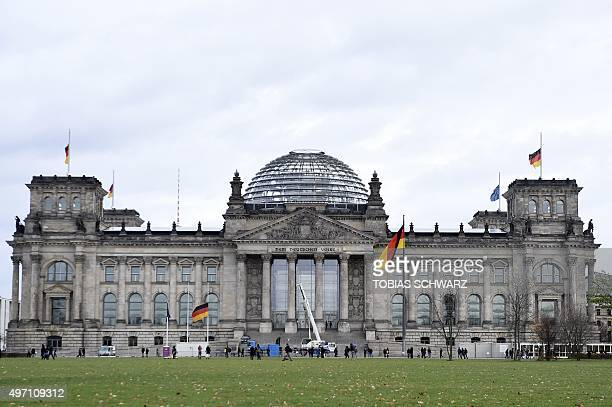 German national flags are seen on half mast on the Reichstag building hosting German lower house of Parliament in Berlin on November 14 2015 in...