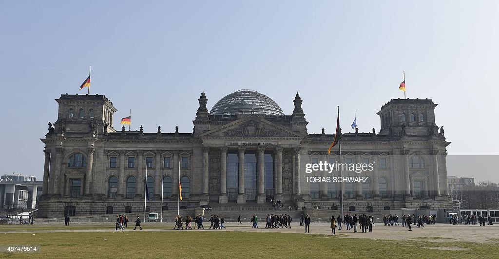 German national flags fly on March 25 2015 at halfmast at the Reichstag building housing the Bundestag in Berlin to commemorate the victims of the...
