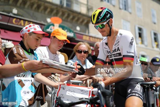 German National Road Race Champion Marcus Burghardt of BoraHansgrohe signs autographs at the start of stage sixteen of the 2017 Tour de France a...