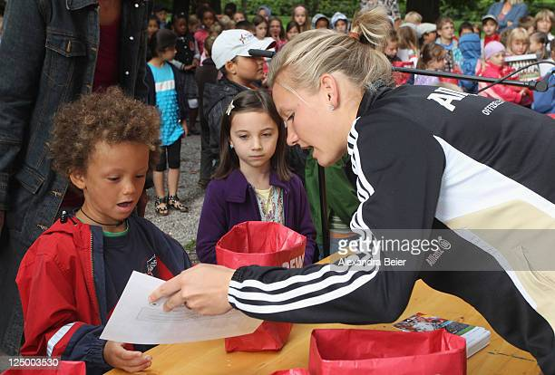 German national soccer player Alexandra Popp hands over a bag filled with healthy food to a first grade pupil on September 15 2011 in Augsburg Germany