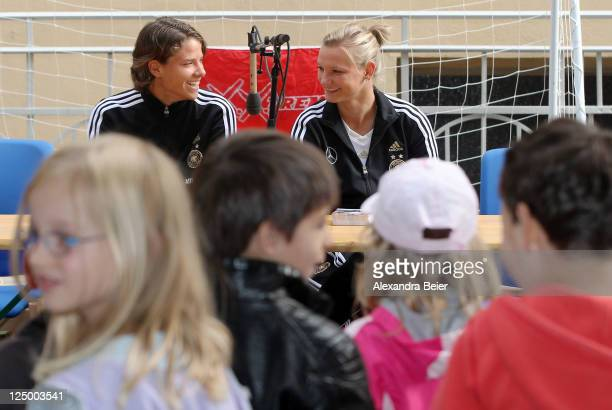 German national soccer players Annike Krahn and Alexandra Popp answer children's questions before they hand over bags filled with healthy food to...