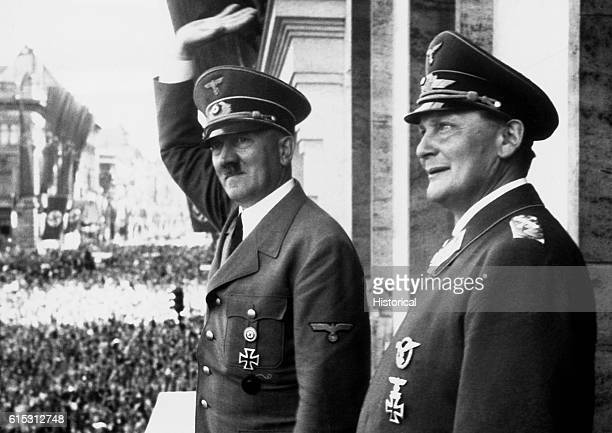 German Nazi party leader Adolf Hitler waves to a crowd from a balcony as Storm Trooper commander and Reichstag president Hermann Goering stands by