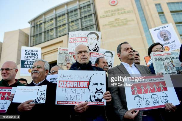 German novelist Gunter Wallraff and protesters hold posters with images of Turkish daily newspaper Cumhuriyet staff members during a demonstration in...