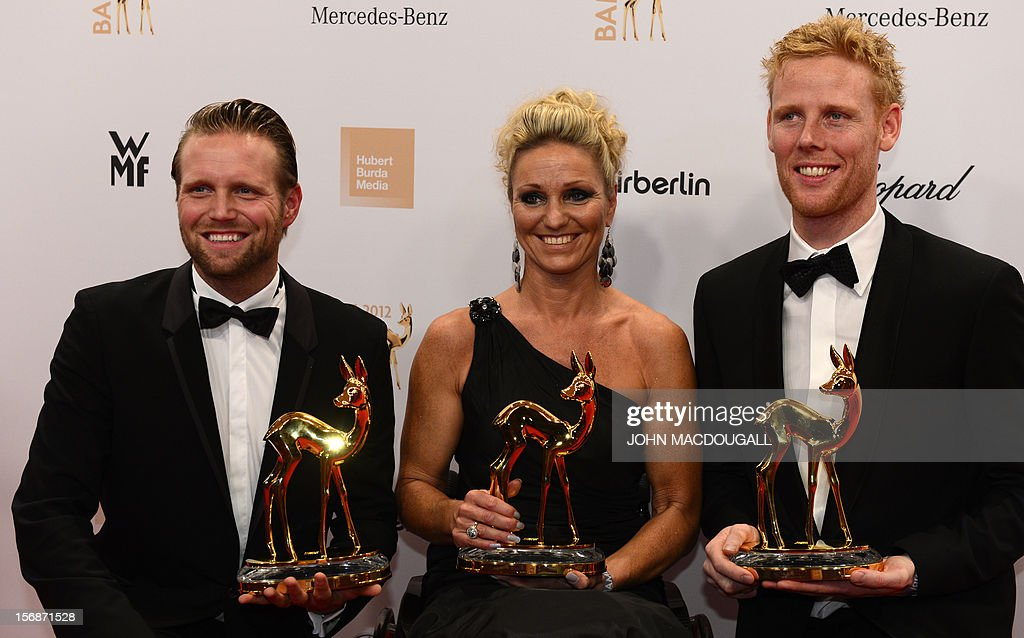 German Paralympics swimming gold medal winner Kirsten Bruhn (C) and German Olympic Games beachvolleyball gold medal winners Julius Brink (L) and Jonas Reckermann (R) pose with their trophies during the Bambi awardings in Duesseldorf, western Germany, on November 22, 2012. The Bambis are the main German media awards.