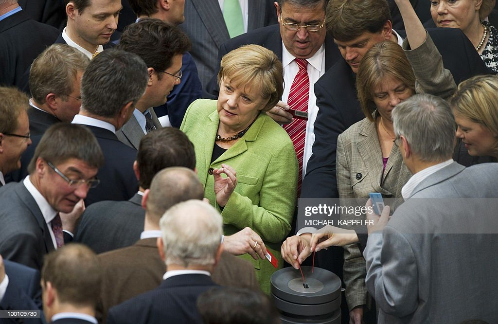 German parliamentarians including Chancellor Angela Merkel vote after a debate at the Bundestag, the lower house of parliament, on May 21, 2010 in Berlin. Parliament's lower house approved the German share of a trillion-dollar rescue package for debt-stricken eurozone countries, after Chancellor Angela Merkel warned the euro was 'in danger'.