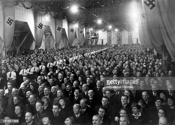 German people of the Sudetenland crowding a room in the Reichenberger decorated with Nazi flags to listen to a speech by Joseph Goebbels German...