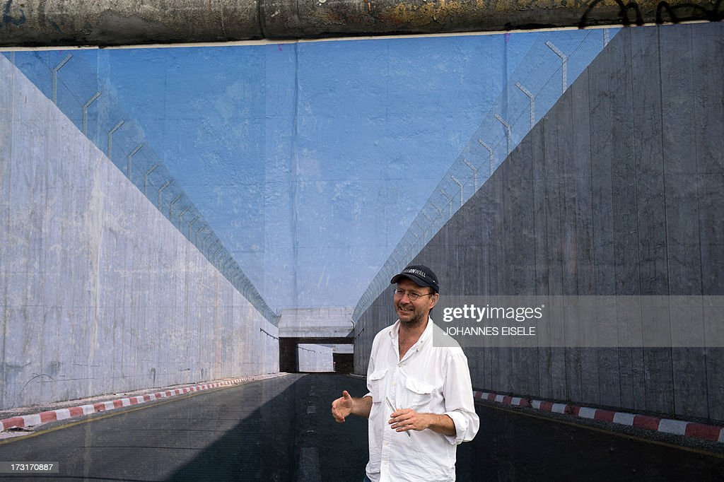 STORY - German photographer Kai Wiedenhoefer stands in front of a panorama picture of the wall in West Bank that is part of his 'Wall on Wall' exhibition on a remaining section of the Berlin Wall in Berlin, Germany on July 9, 2013. The 'Wall on Wall' project by award-winning German photographer Kai Wiedenhoefer features giant panoramas taken in Northern Ireland, Iraq, Cyprus, the West Bank, Morocco, South Korea and the border zone between the United States and Mexico.