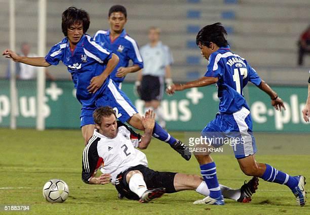 German player Andreas Hindkel tries to block Thai attackers Yuttajak Kongjan and Kittisak Siriwan in the first half of a friendly match in Bangkok 21...