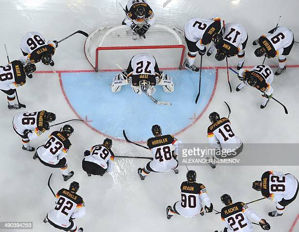 German players gather around their goalkeeper during a IIHF International Ice Hockey World Championship preliminary round group B game between...