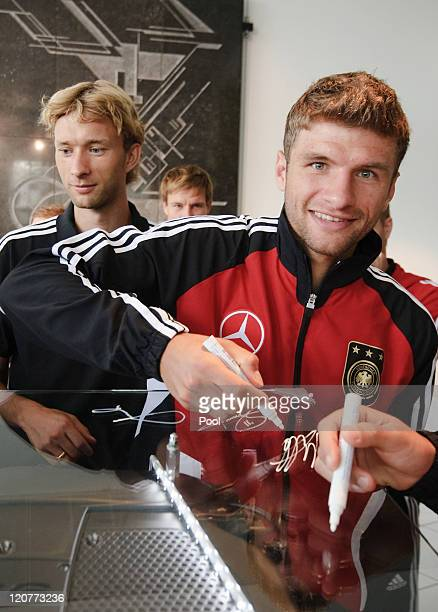 German players Simon Rolfes and Thomas Mueller sign an engine during a visit of the German national football team at the MercedesBenz engine factory...