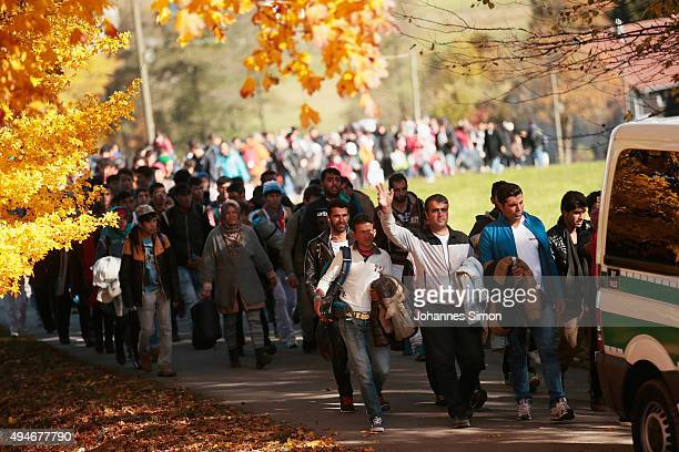 German police lead arriving migrants alongside a street to a transport facility after gathering them at the border to Austria on October 28 2015 near...
