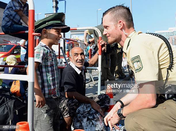 German police officer and a migrant boy joke with the officer's cap while migrants wait for a bus after their arrival at the main train station in...