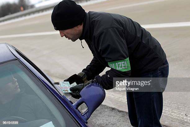 German police officer controls an identity card of a Czech traveller during a dragnet control on February 8 2010 in Schwandorf Germany Czech and...