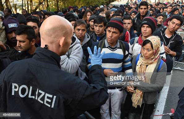 A German police officer speaks with migrants waiting to cross the AustrianGerman border near the Bavarian town of Passau southern Germany on October...