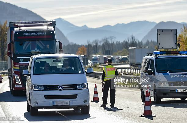 A German police officer survey cars and trucks queuing to cross a border control between Austria and Germany at the southern German city of...