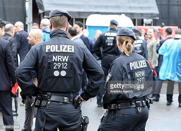 German police officers stand guard as thousands of Turkish people living in Europe attend prodemocracy rally in Cologne on July 31 2016 to protest...