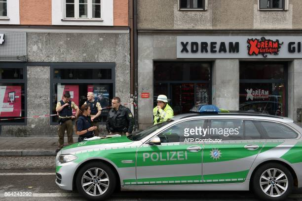 German police officers stand next to their vehicle inside a security perimeter that was set after a man attacked passersby near Rosenheimer square in...