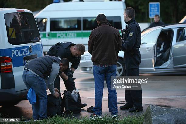 German police question and search three men from Iraq whom they found in the car of a suspected smuggler at a police checkpoint near the border to...