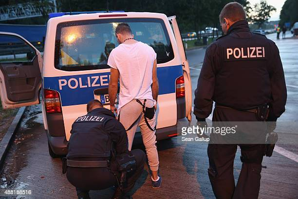 German police search a Swedish national they suspected of attempting to smuggle three men from Iraq into Germany at a police checkpoint near the...