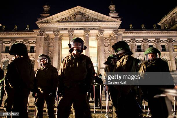 German police stands guard in front of the Reichstag as protesters demonstrating against the influence of bankers and financiers in front of the...