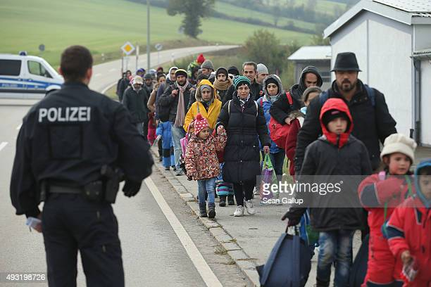 German policeman directs migrants who had walked across the nearby border from Austria on October 17 2015 in Wegscheid Germany According to a German...