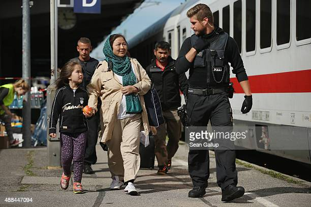 German policeman escorts a family from Afghanistan who had arrived with migrants on a regular train from Vienna Austria and told to disembark by...