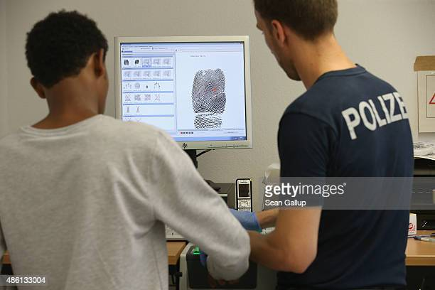 German policeman takes a fingerprint scan of a newlyarrived migrant as part of the registration process at a center for migrants at a facility of the...