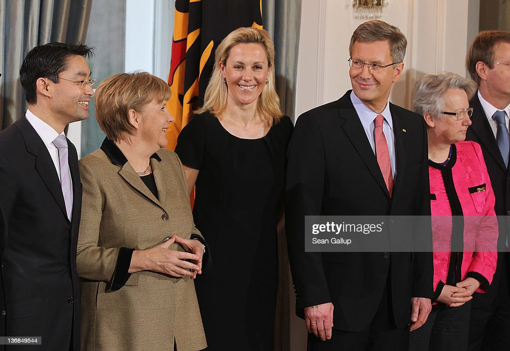 German President Christan Wulff (4th from L) and his wife Bettina Wulff (3rd from L) receive members of the German government, including German Chancellor Angela Merkel (2nd from L), at the annual Presidential New Year's reception for citizens and public servants at Schloss Bellevue palace on January 12, 2012 in Berlin, Germany. Wulff says he refuses to resign despite mounting criticims over a personal loan he took while he was governor of Lower Saxony as well as accusations that he attempted to block Bild Zeitung tabloid from publishing a story about the loan.