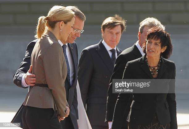 German President Christian Wulff puts his arm around his wife First Lady Bettina Wulff as Swiss President Doris Leuthard looks on on Wulff's first...