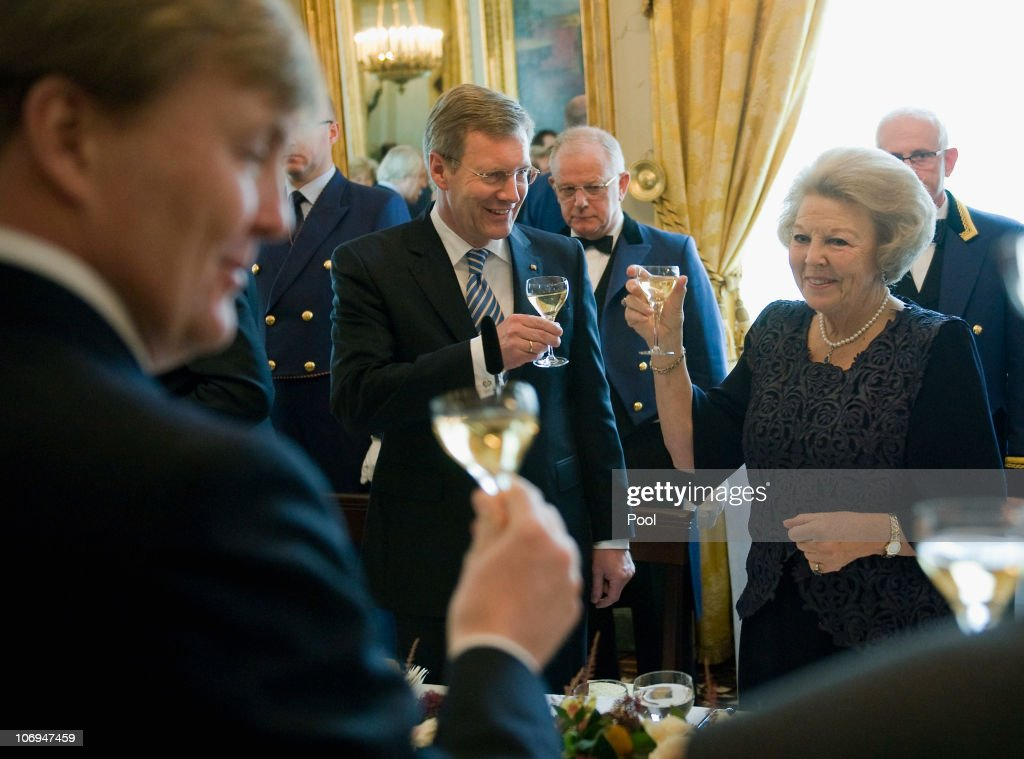 German President <a gi-track='captionPersonalityLinkClicked' href=/galleries/search?phrase=Christian+Wulff&family=editorial&specificpeople=221618 ng-click='$event.stopPropagation()'>Christian Wulff</a> (C) toasts with a glass of champagne with Queen <a gi-track='captionPersonalityLinkClicked' href=/galleries/search?phrase=Beatrix+of+the+Netherlands&family=editorial&specificpeople=92396 ng-click='$event.stopPropagation()'>Beatrix of the Netherlands</a> (R) as Willem Alexander of the Netherlands (L) smiles during a reception at Huis ten Bosch Palace on November 18, 2010 in The Hague, Netherlands. German President Wulff is on a one-day-visit to the Netherlands.