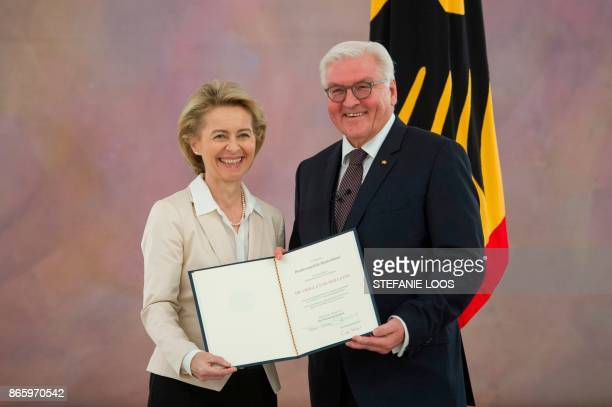 German President FrankWalter Steinmeier hands over the certificates of discharge to outgoing German Defence Minister Ursula von der Leyen at the...