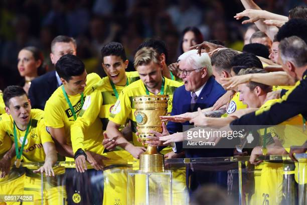German President FrankWalter Steinmeier hands over the trophy to team captain Marcel Schmelzer of Dortmund after the DFB Cup Final between Eintracht...
