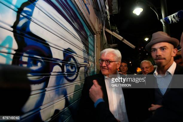 German President FrankWalter Steinmeier stands next to a graffiti depicting Israeli President Reuven Rivlin's greatgrandfather as he visits the...
