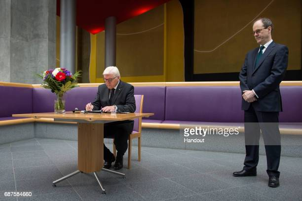 German President FrankWalter Steinmeier writes in a book of condolence to commemorate the victims of the attack in Manchester as British Ambassador...