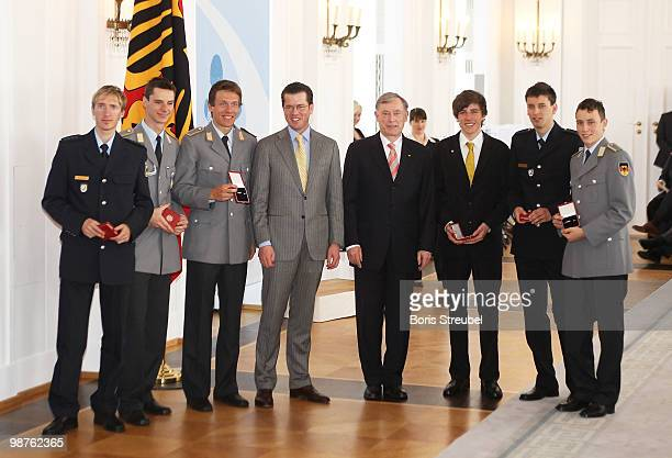 German President Horst Koehler and German Defense Minister KarlTheodor zu Guttenberg pose with Michael Uhrmann and Andreas Wank of the German flying...