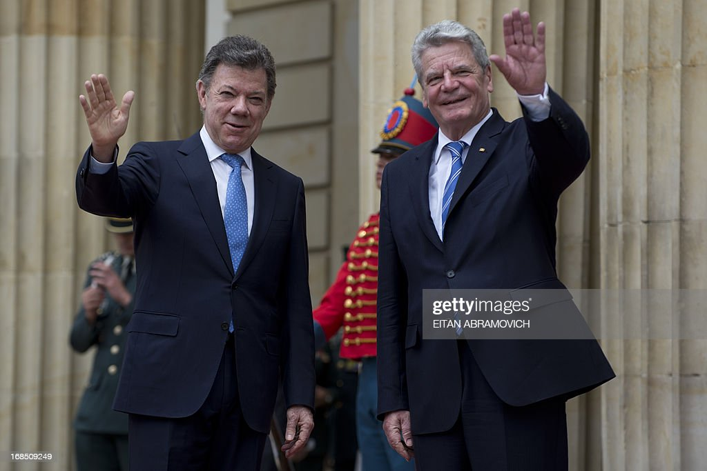 German President Joachim Gauck (R) and his Colombian counterpart Juan Manuel Santos wave to journalists during a welcoming ceremony at Narino Presidential Palace in Bogota, Colombia, on May 10, 2013. Gauck is on a four-day official visit to Colombia. AFP PHOTO/Eitan Abramovich