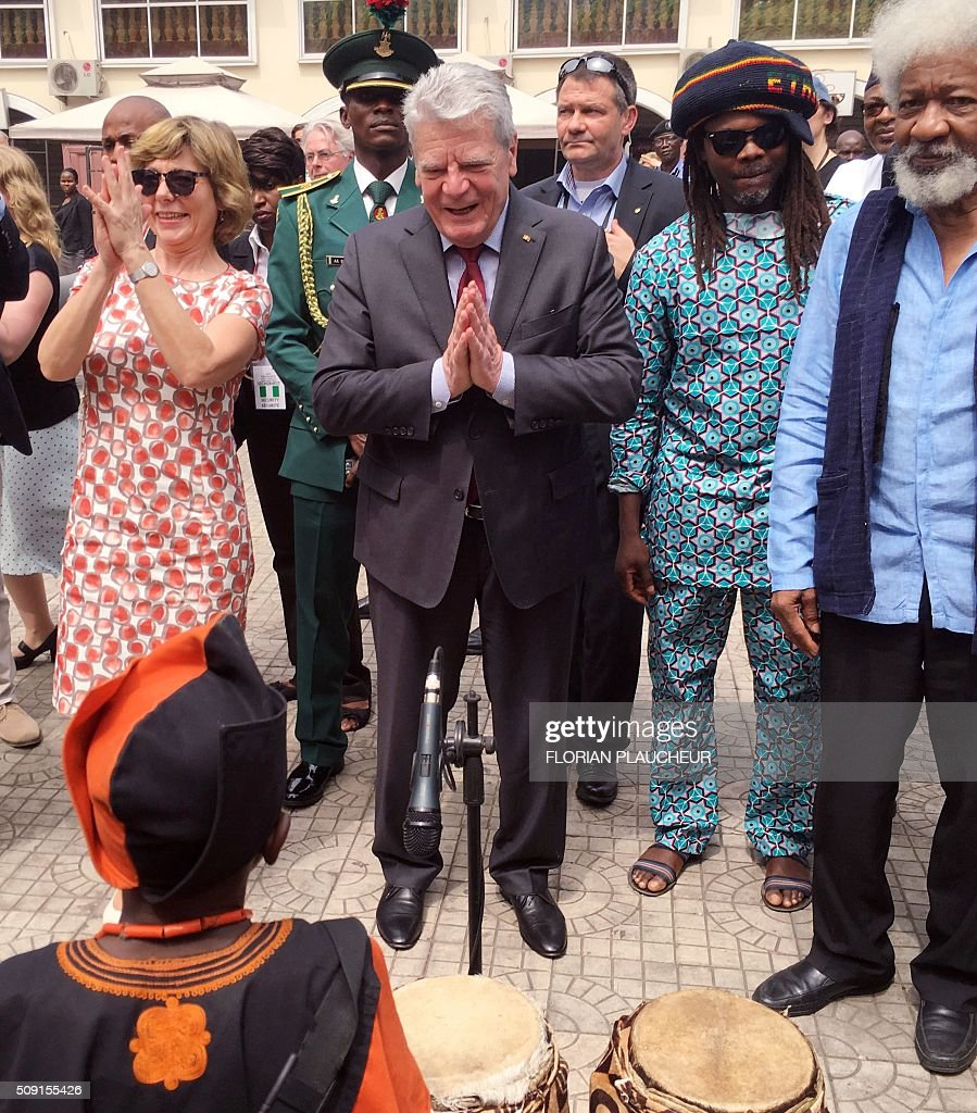 German President Joachim Gauck (C) and his wife Gerhild (L) applaud beside playwright Professor Wole Soyinka (R) after dancing with a cultural troupe at the Freedom Park in Lagos, on February 9, 2016. Gauck, accompanied by his wife and top government functionaries as well as strong delegation from the business community, is in Nigeria to strengthen cooperation between the two countries. / AFP / FLORIAN PLAUCHEUR