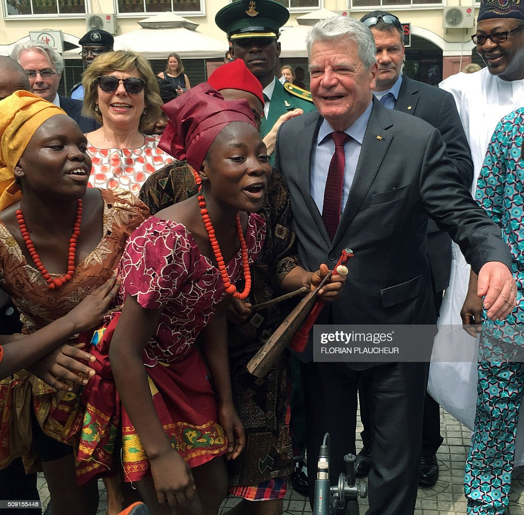 German President Joachim Gauck (R) and his wife Gerhild dance with a cultural troupe at the Freedom Park in Lagos, on February 9, 2016. Gauck, accompanied by his wife and top government functionaries as well as strong delegation from the business community, is in Nigeria to strengthen cooperation between the two countries. / AFP / FLORIAN PLAUCHEUR