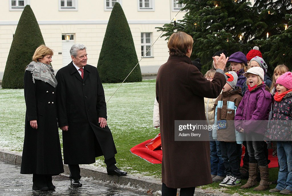 German President Joachim Gauck (2 from L) and his partner Daniela Schadt (L) listen to Christmas carols being sung by students of the Carl von Ossietzky school during the illumination ceremony for the Christmas tree at Bellevue Presidential Palace on December 4, 2012 in Berlin, Germany. The 12-meter (40-foot) tall Colorado blue spruce (Picea pungens) was planted in 1994 and is being supplied to the president for the second time by Werderaner Tannenhof Christmas tree farm in the town of Werder, just outside of the German capital.