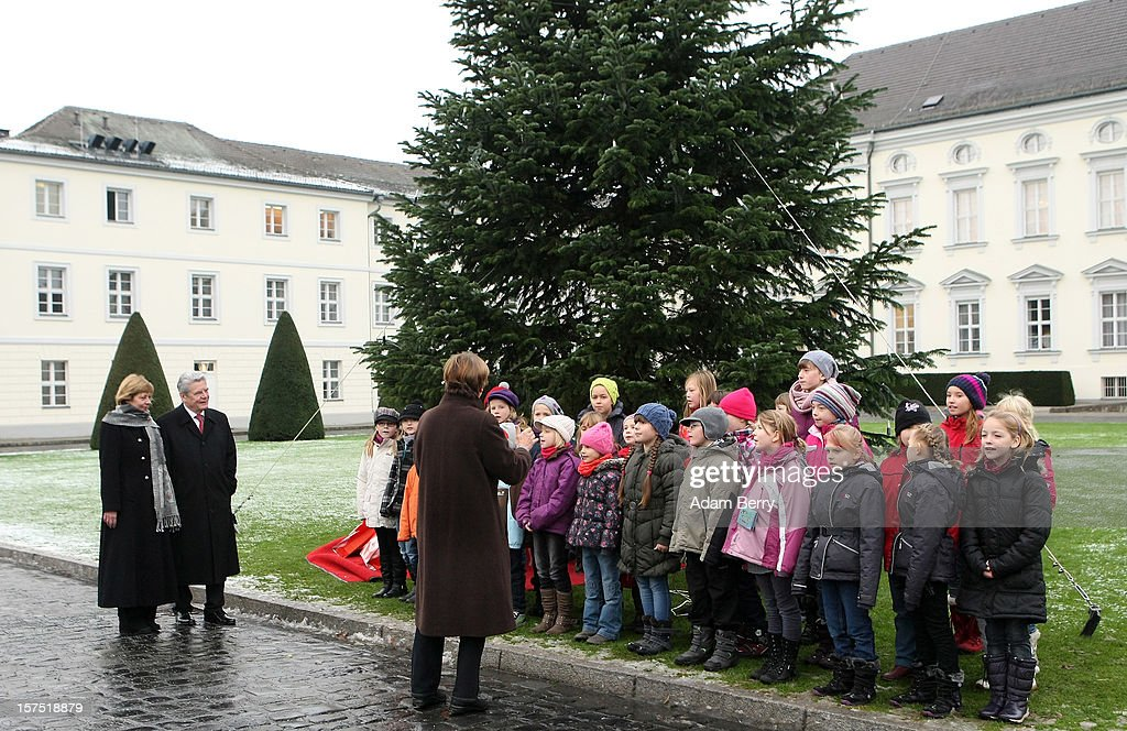 German President Joachim Gauck (2nd from R) and his partner Daniela Schadt (L) listen to Christmas carols being sung by students of the Carl von Ossietzky school during the illumination ceremony for the Christmas tree at Bellevue Presidential Palace on December 4, 2012 in Berlin, Germany. The 12-meter (40-foot) tall Colorado blue spruce (Picea pungens) was planted in 1994 and is being supplied to the president for the second time by Werderaner Tannenhof Christmas tree farm in the town of Werder, just outside of the German capital.
