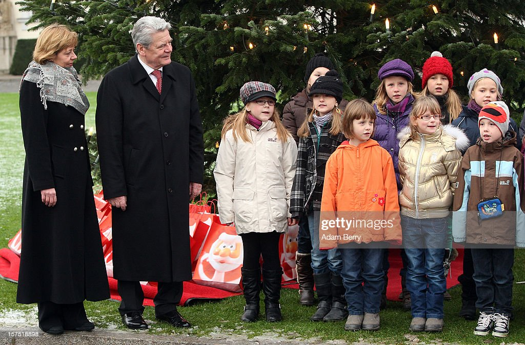 German President <a gi-track='captionPersonalityLinkClicked' href=/galleries/search?phrase=Joachim+Gauck&family=editorial&specificpeople=2077888 ng-click='$event.stopPropagation()'>Joachim Gauck</a> (2nd from R) and his partner Daniela Schadt (L) listen to Christmas carols being sung by students of the Carl von Ossietzky school during the illumination ceremony for the Christmas tree at Bellevue Presidential Palace on December 4, 2012 in Berlin, Germany. The 12-meter (40-foot) tall Colorado blue spruce (Picea pungens) was planted in 1994 and is being supplied to the president for the second time by Werderaner Tannenhof Christmas tree farm in the town of Werder, just outside of the German capital.