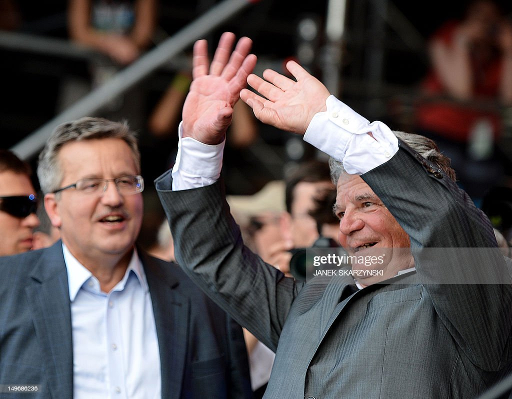 German President Joachim Gauck (R) and his Polish counterpart Bronislaw Komorowski wave to the public during a opening of music festival 'Woodstock festival Poland' in Kostrzyn nad Odra on August 2, 2012.