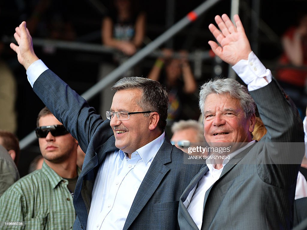 German President Joachim Gauck (R) and his Polish counterpart Bronislaw Komorowski wave to public during a opening of music festival 'Woodstock festival Poland' in Kostrzyn nad Odra on August 2, 2012.