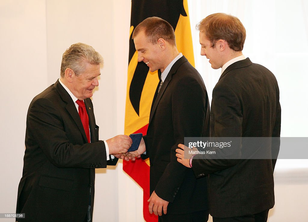 German President <a gi-track='captionPersonalityLinkClicked' href=/galleries/search?phrase=Joachim+Gauck&family=editorial&specificpeople=2077888 ng-click='$event.stopPropagation()'>Joachim Gauck</a> (L) awards Germany's silver medalist Kai Kristian Kruse (C) the Silbernes Lorbeerblatt during the 'Silbernes Lorbeerblatt Award Ceremony' at Schloss Bellevue on November 7, 2012 in Berlin, Germany.