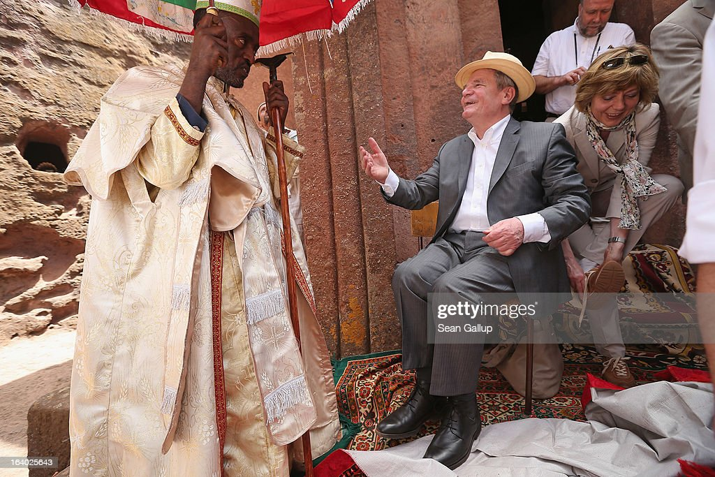German President Joachim Gauck chats with an Ethiopian Orthodox clergyman after he put his shoes back on following a visit to St. George's Church as First Lady Daniela Schadt finishes putting her shoes back on on March 19, 2013 in Lalibela, Ethiopia. All visitors are requires to remove their shoes before entering the church at Lalibela. Lalibela is among Ethiopia's holiest of cities and is distinguished by its 11 churches hewn into solid rock that date back to the 12th century. President Gauck and First Lady Daniela Schadt are on the third of a four-day state visit to Ethiopia.