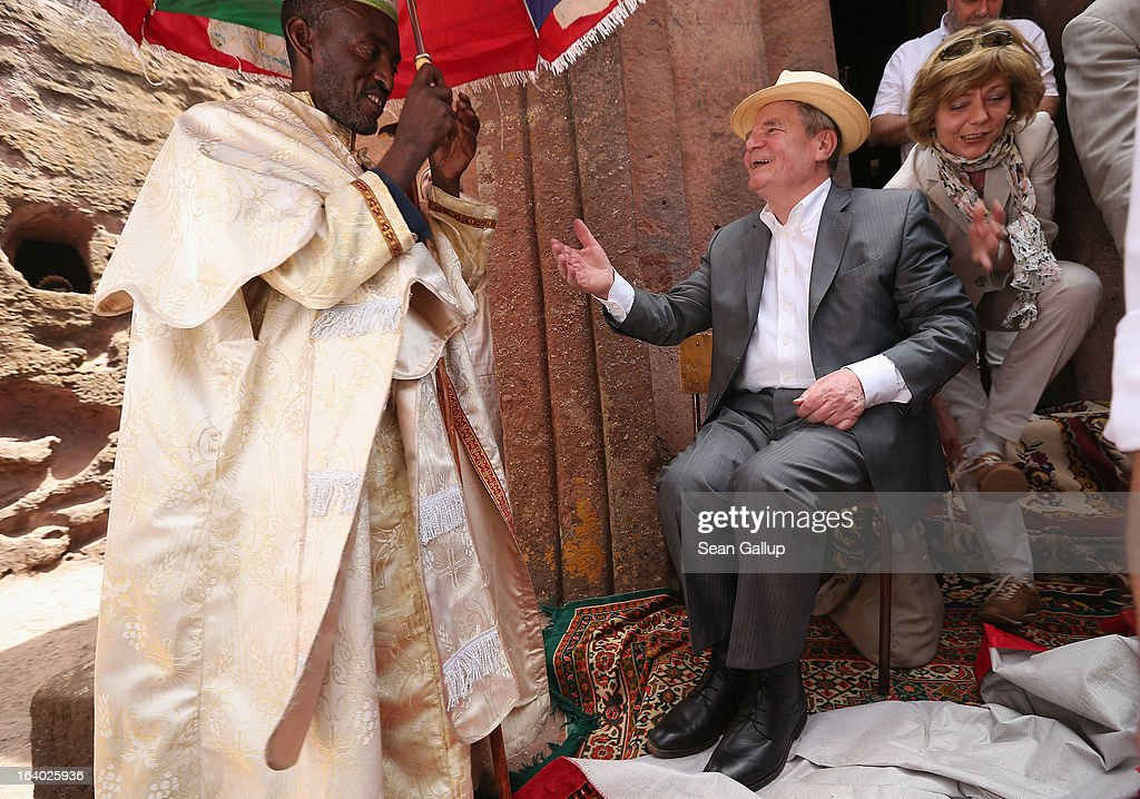 German President Joachim Gauck chats with an Ethiopian Orthodox clergyman after he put his shoes back on following a visit to St. George's Church as First Lady Daniela Schadt finishes putting her shoes back on on March 19, 2013 in Lalibela, Ethiopia. All visitors are required to remove their shoes before entering the churches at Lalibela. Lalibela is among Ethiopia's holiest of cities and is distinguished by its 11 churches hewn into solid rock that date back to the 12th century. President Gauck and First Lady Daniela Schadt are on the third of a four-day state visit to Ethiopia.