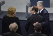 German President Joachim Gauck cheers French President Francois Hollande next to German Chancellor Angela Merkel during a joint session of the French...